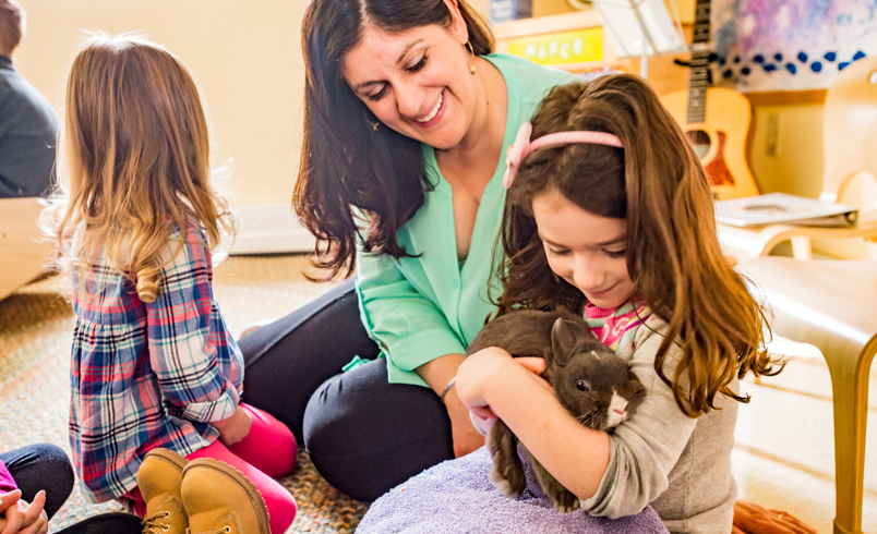 a_nursery_teacher_with_two_children_one_of_them_holding_a_bunny